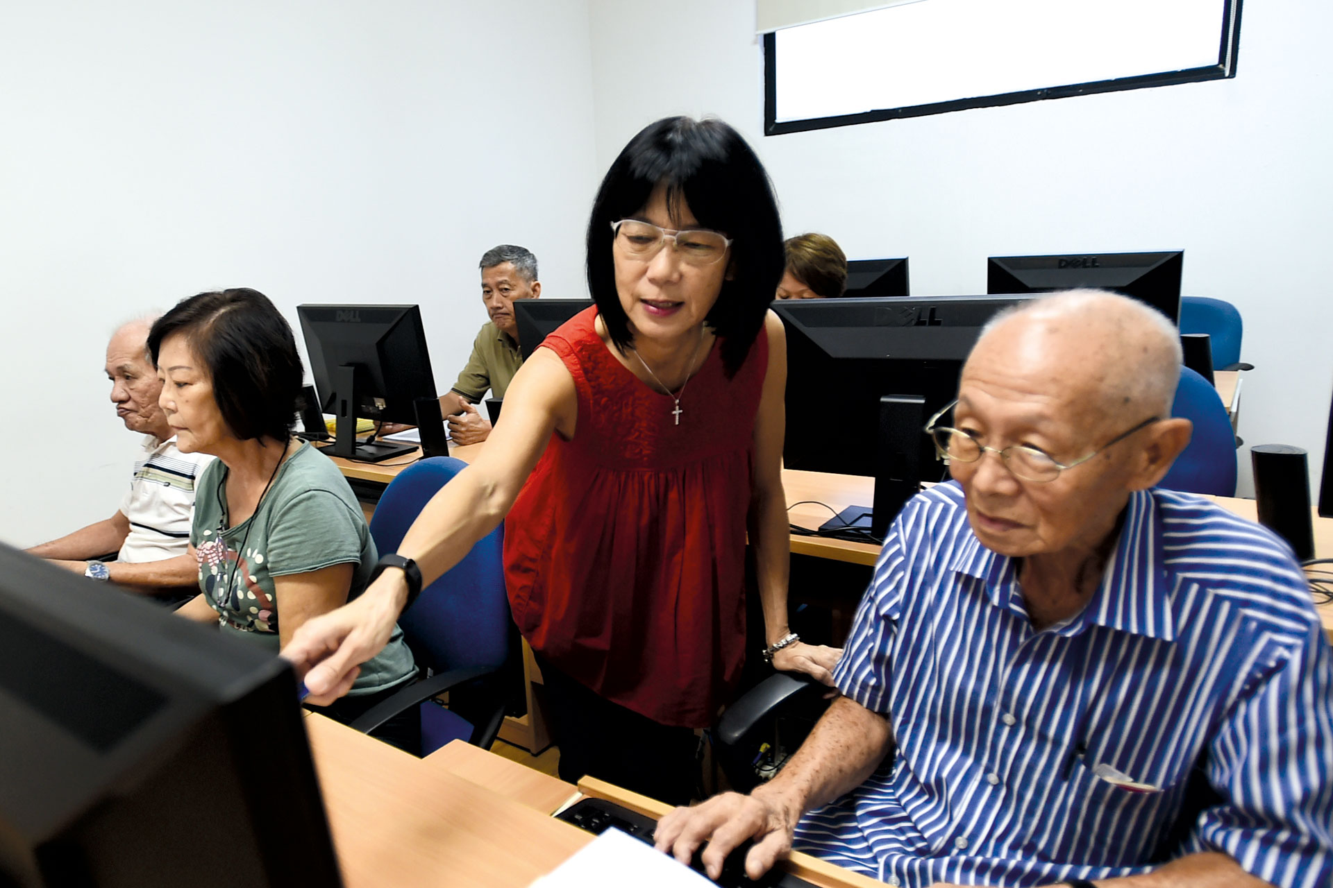 Mdm Ng guides the elderly in using computers.