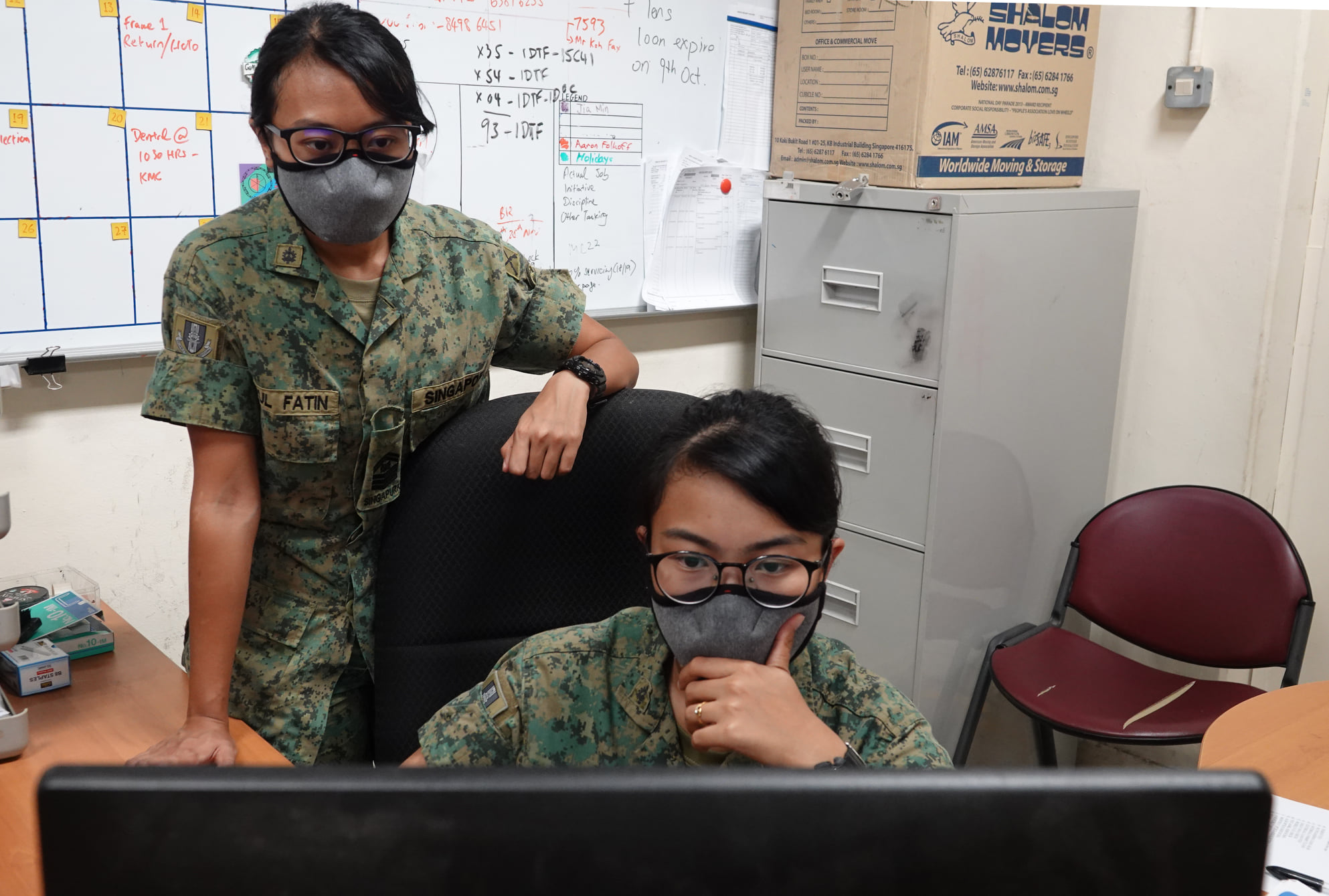 SSG Fatin (right) and 1SG Aini (left) making sure the logistic needs of the units are always met so that they can train seamlessly.