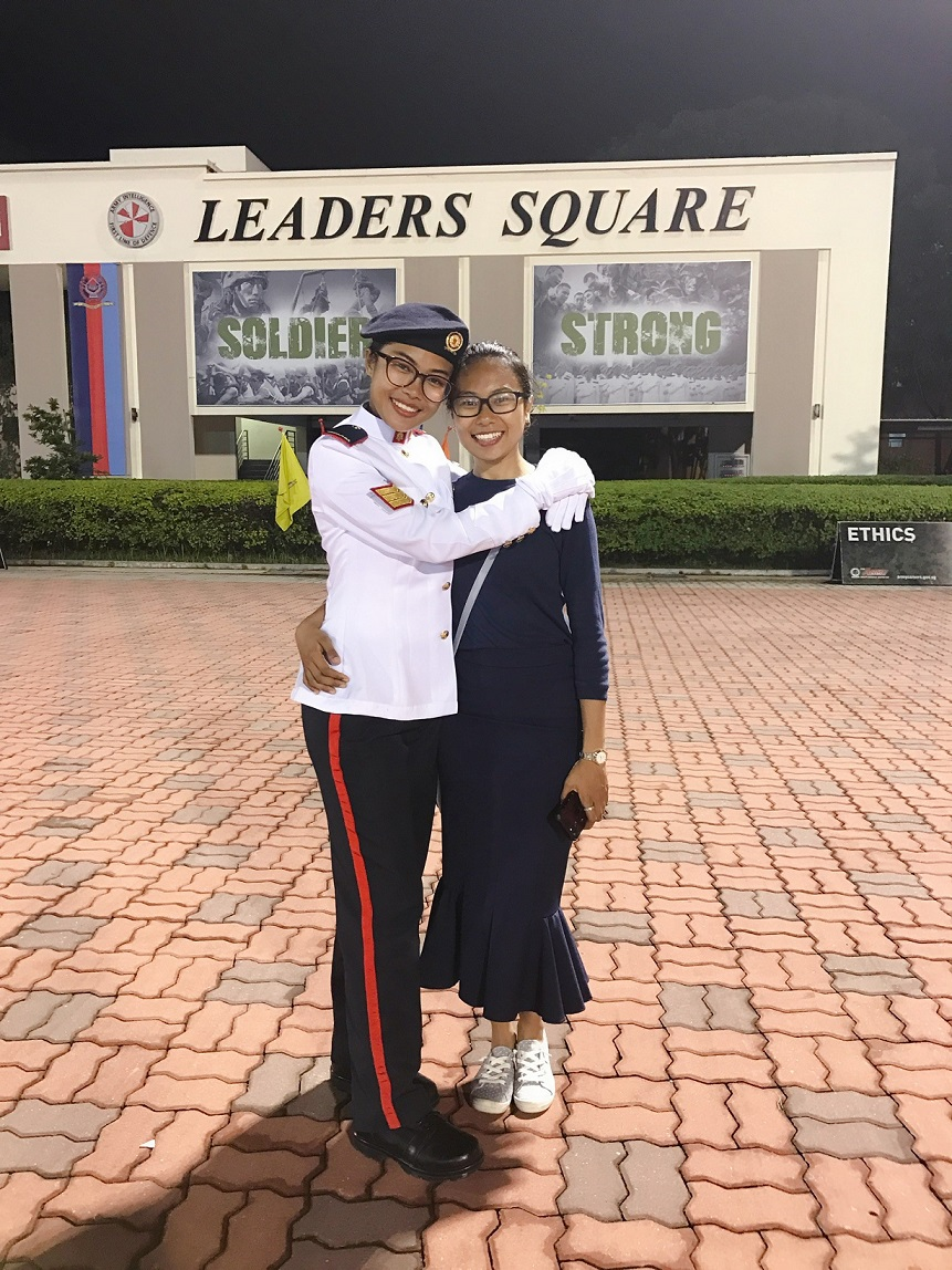 1SG Aini (left) with her sister (right) during her Specialist Cadet Graduation Parade.