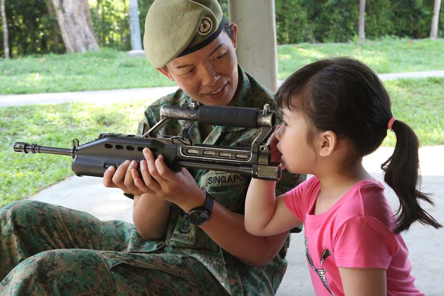3WO Xandra showing her daughter, Iris Lee, how the Singapore Assault Rifle - 21st Century works.