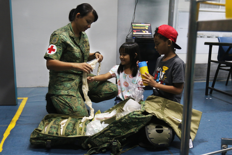 ME2 Salizah sharing with her two children what she does in her daily work as a senior medic.