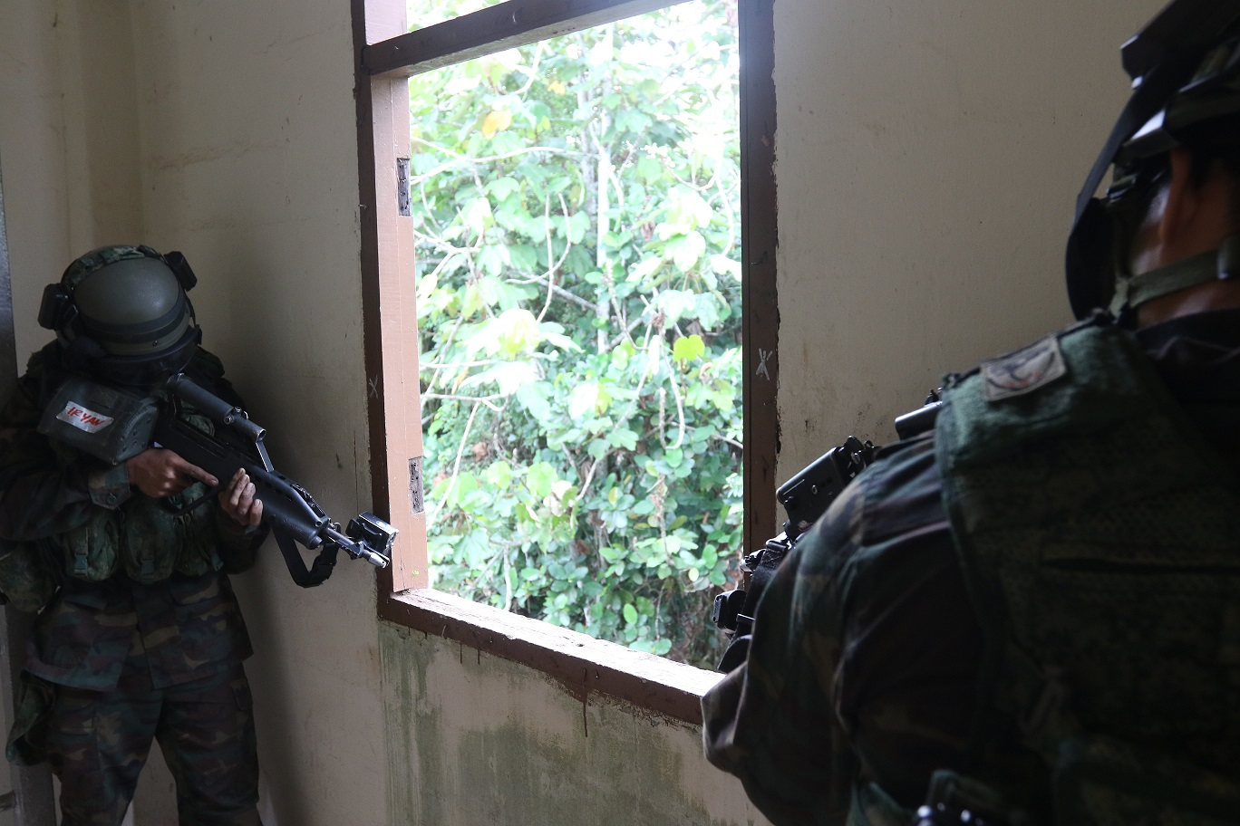 OPFOR soldiers taking cover and aiming in the building.