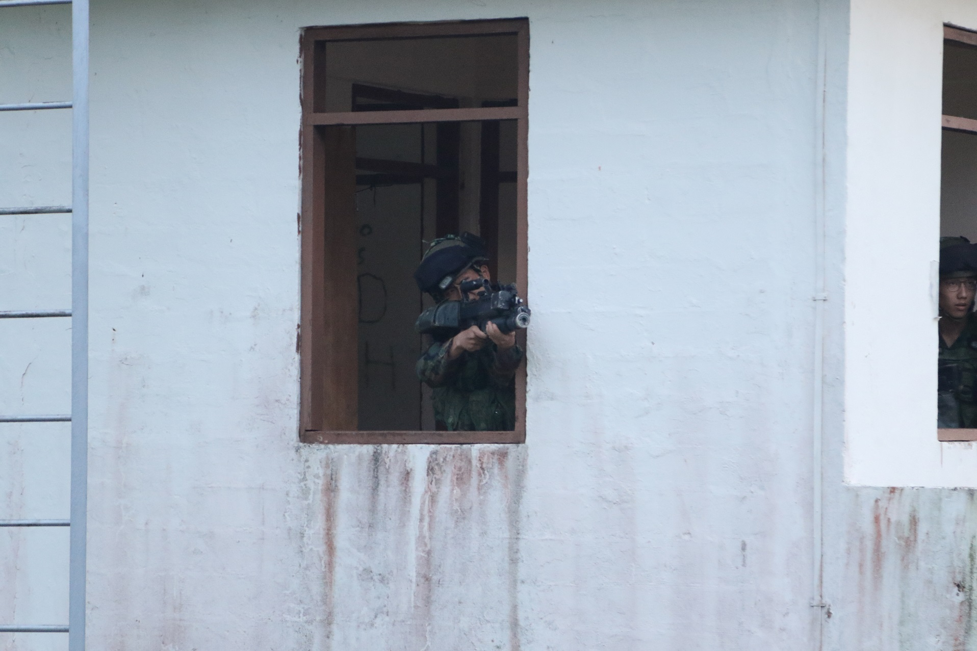 One of the OPFOR soldiers taking cover in the building.