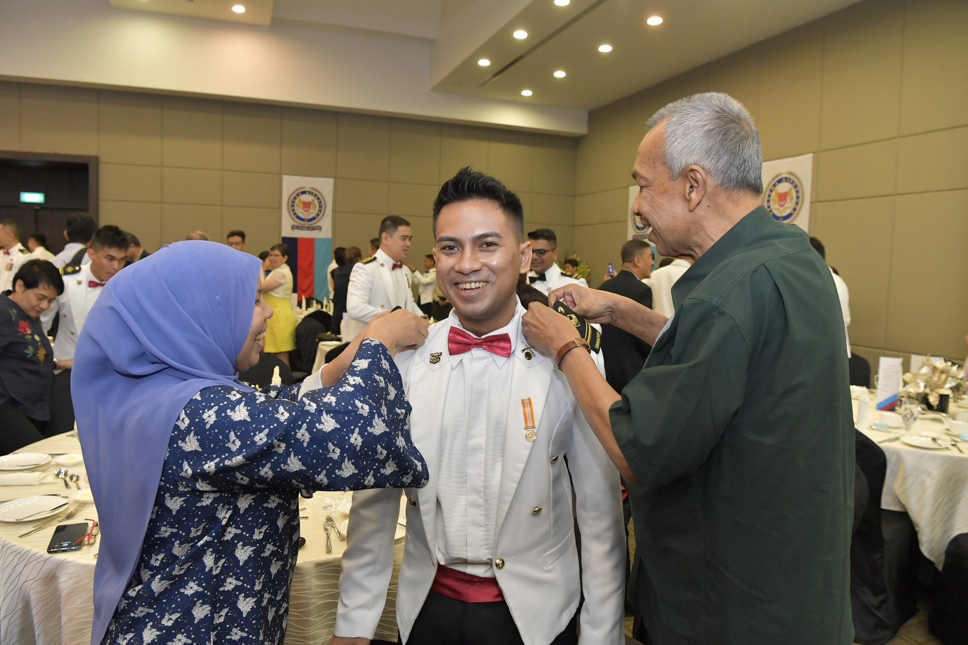 ME4A(NS) Mohamad Zaki Khan Bin Zulkafri's parents putting the ME4 rank epaulette on him.