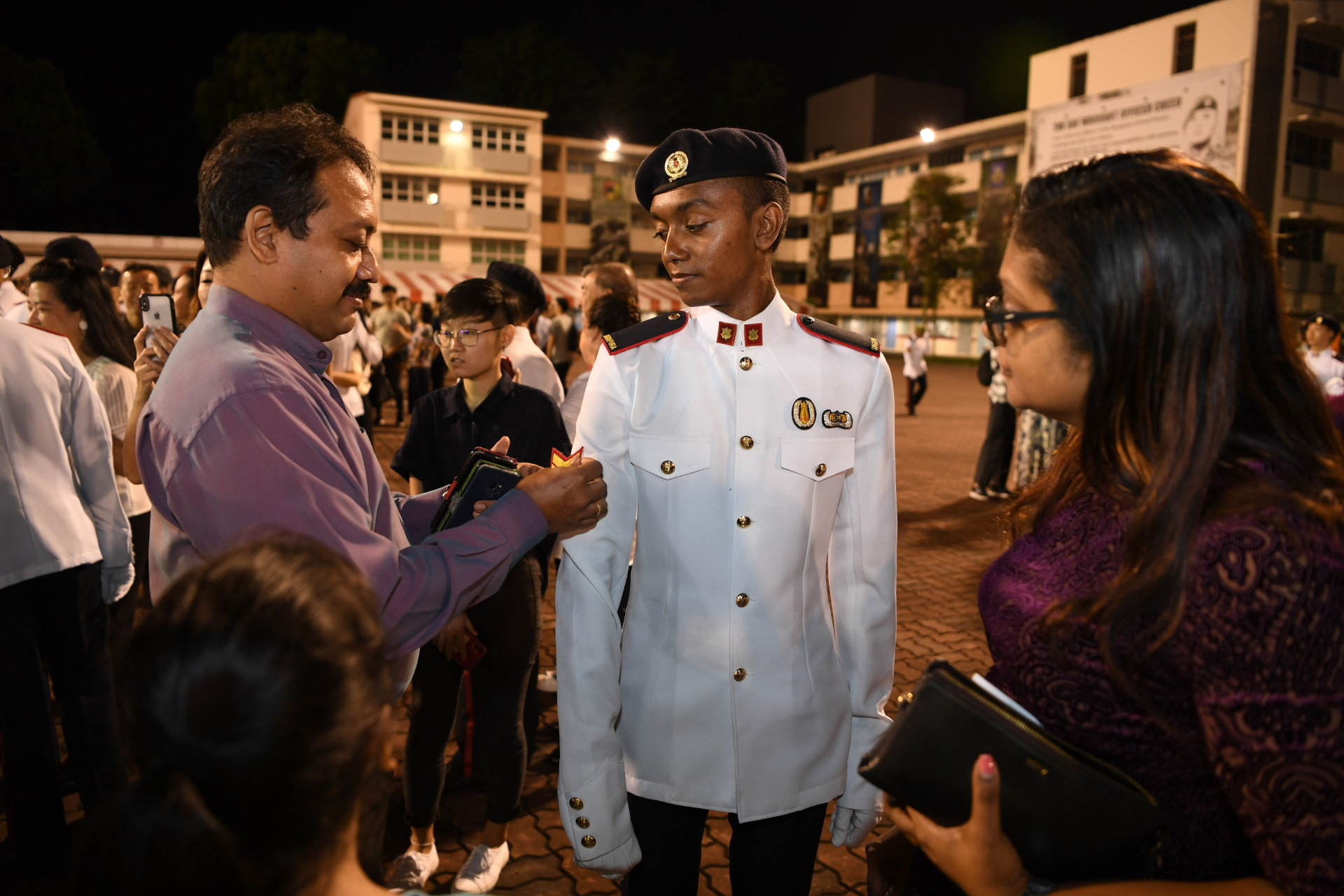 3SG Rammdarshan S/O Ramesh's father affixing the 3rd Sergeant rank on to his uniform at the parade.