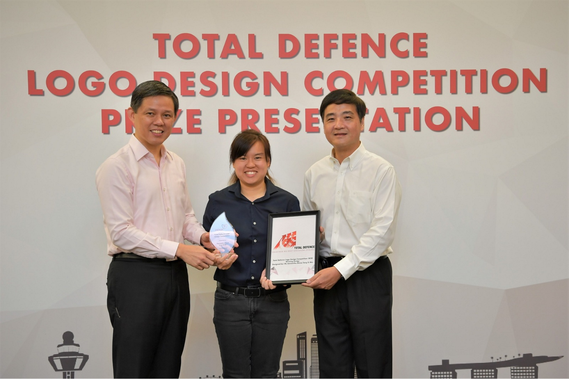 Mr Chan (left) and Senior Minister of State for Defence Mr Heng Chee How (right) presenting an award to the winner of the Total Defence Logo Design Competition, Ms Samantha Teng.