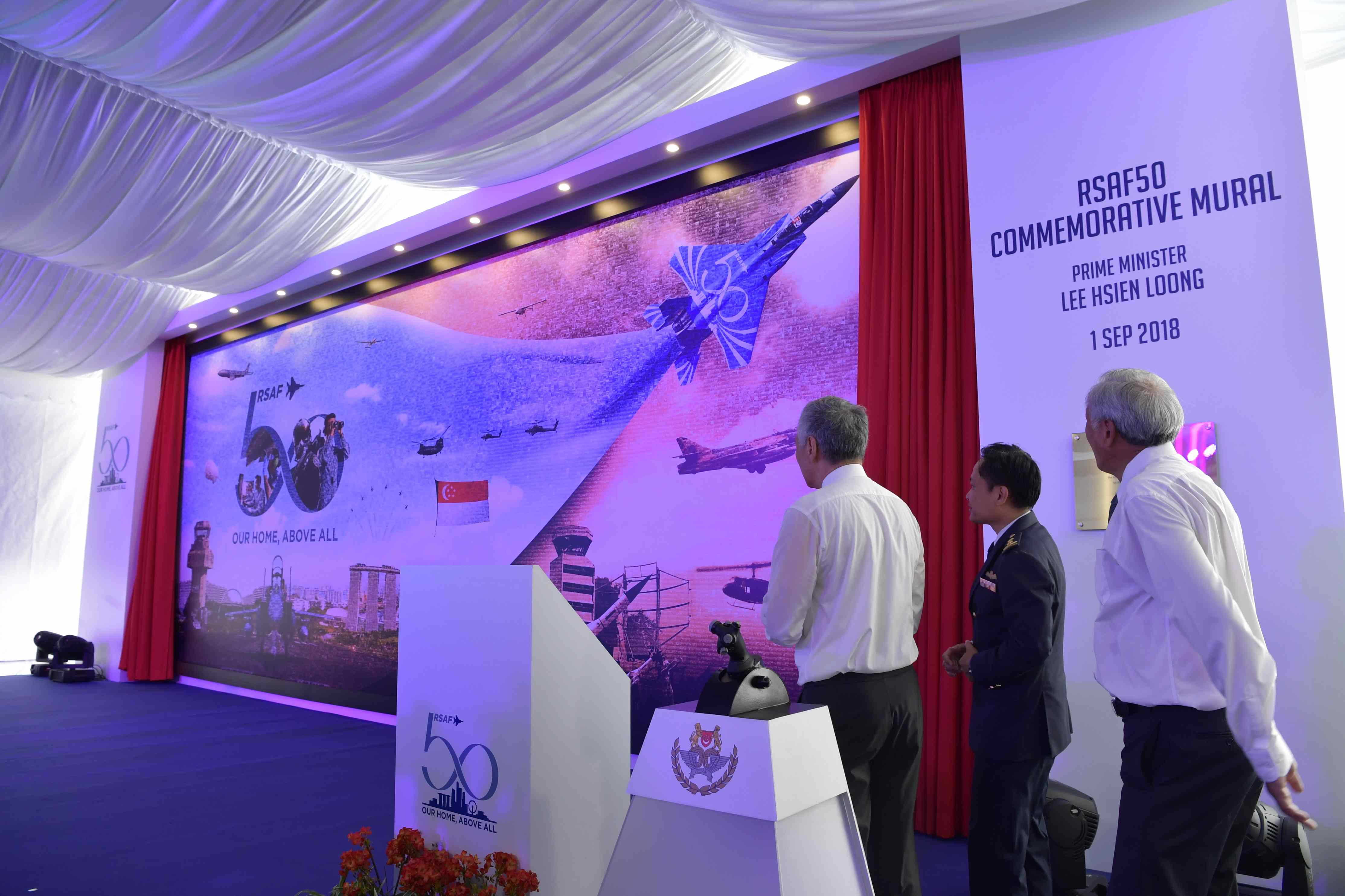PM Lee (left), Chief of Air Force Major-General Mervyn Tan (centre), and Minister for Defence Dr Ng Eng Hen (right) unveiling the RSAF50 Commemorative Mural.