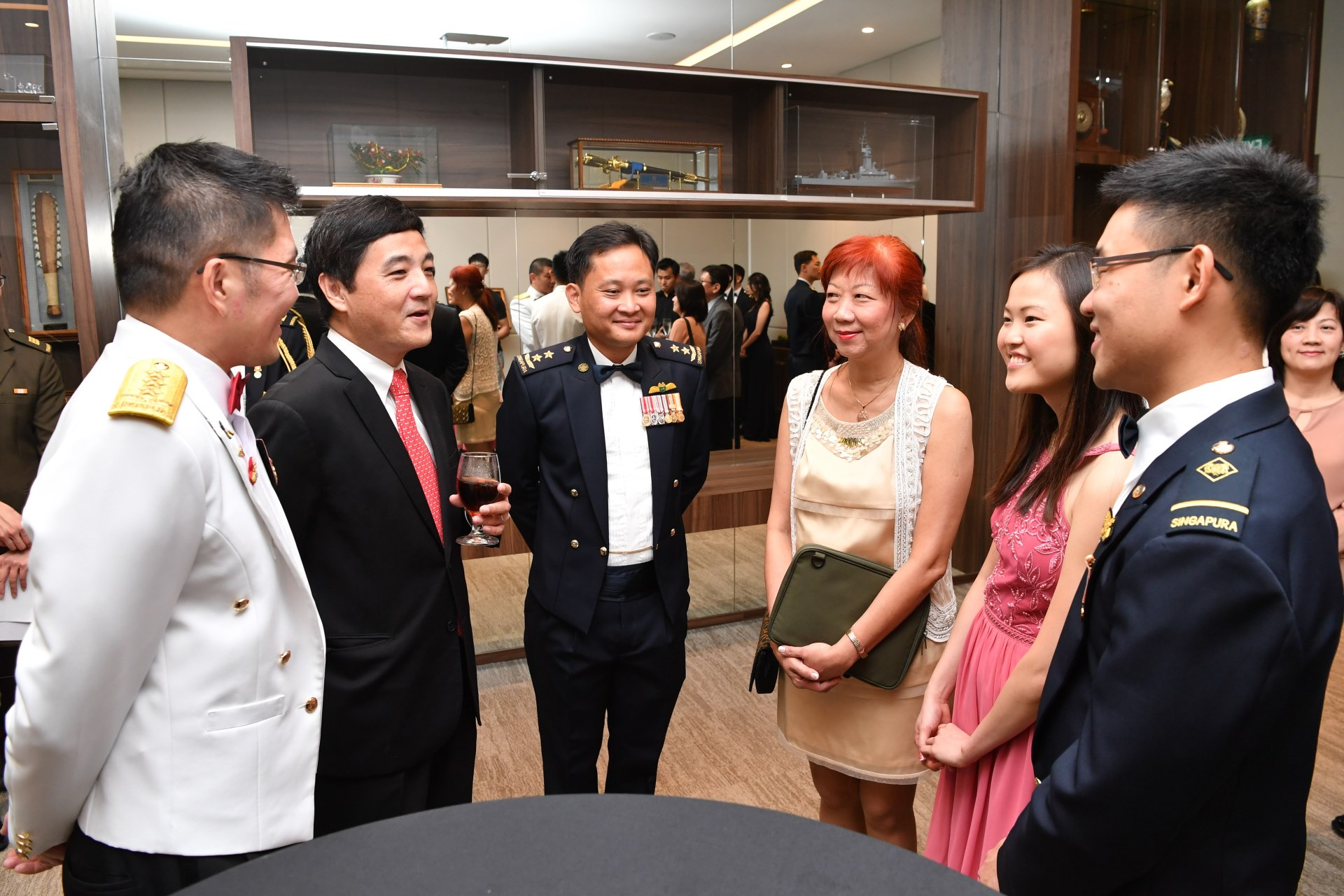 Mr Heng with Chief of Defence Force Lieutenant-General Melvyn Ong and Chief of Air Force Major-General Mervyn Tan interacting with ME4 Ng Zhi Long Benjamin and his family prior to the ceremony at Temasek Club this evening.