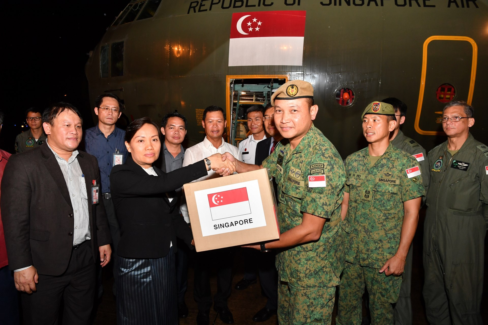 The Singapore Armed Forces (SAF) Mission Commander handing over humanitarian supplies to Laos Vice Minister of Labour and Social Welfare H.E. Baykham Khattiya.
