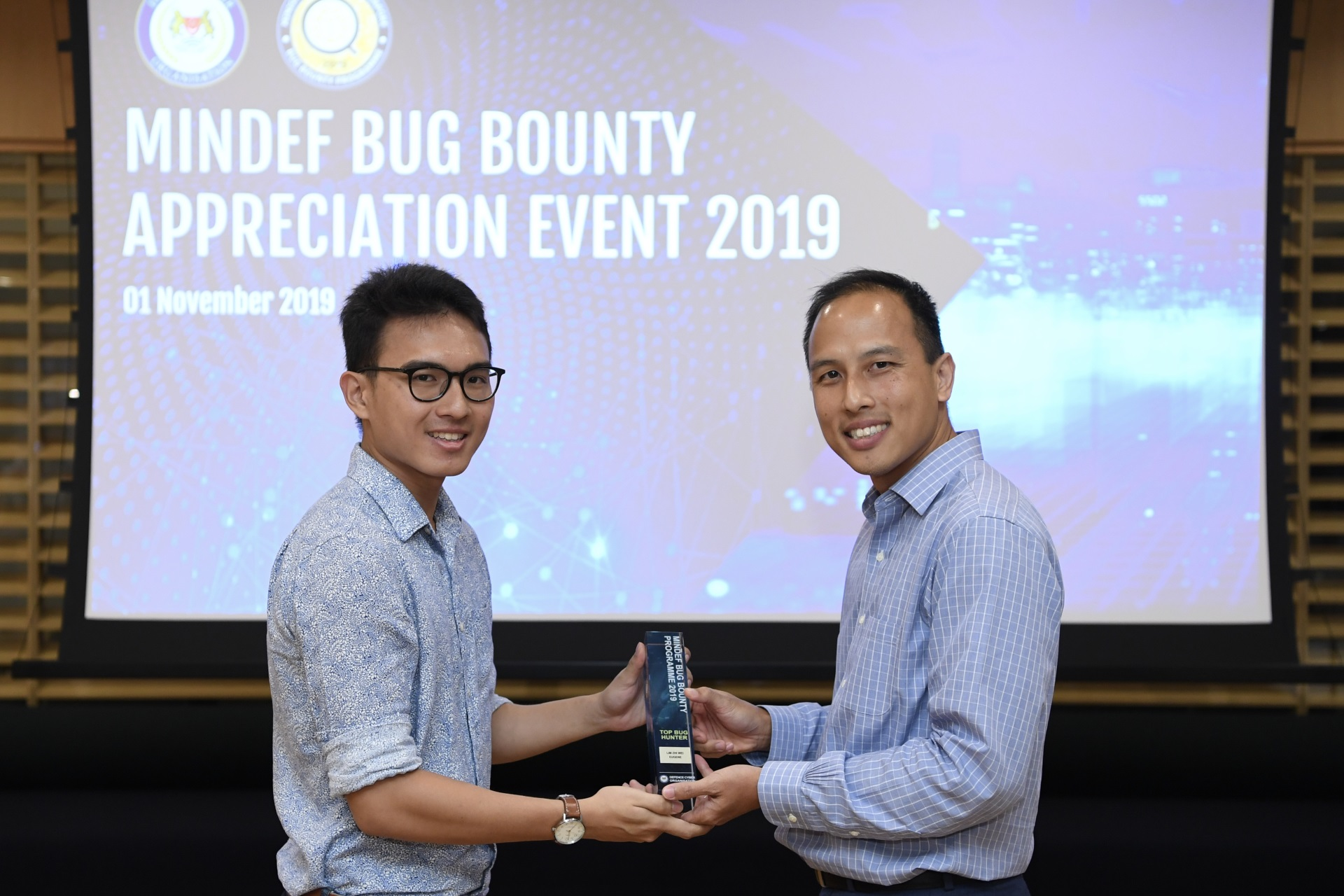 Defence Cyber Chief Brigadier-General (BG) Mark Tan presenting the Top Bug Hunter Award to Mr Eugene Lim at the Bug Bounty Appreciation Event held earlier today.