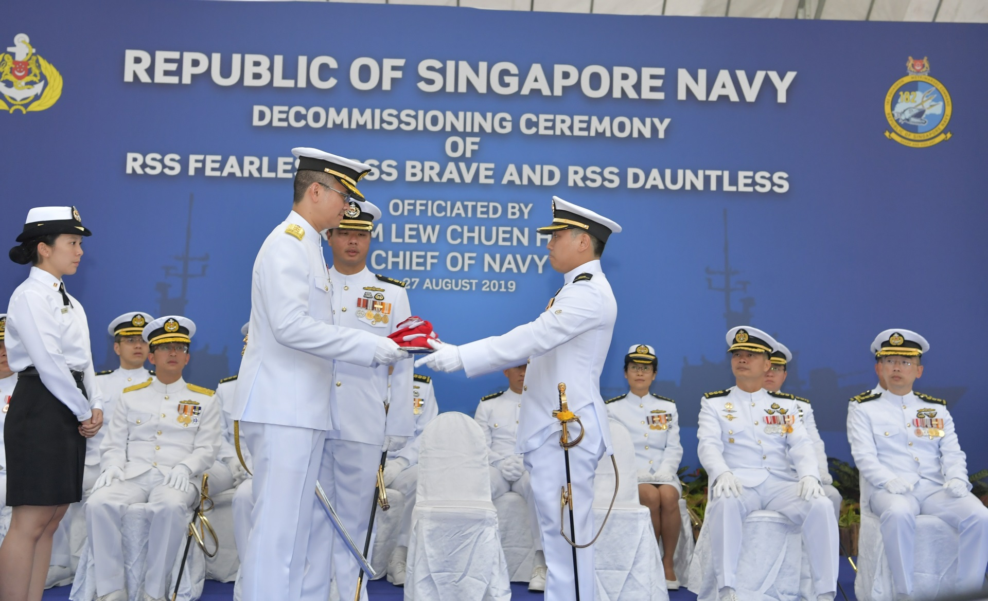 Commanding Officer RSS Fearless, Major Sin Zhenrui presenting RSS Fearless's jack, ensign and commissioning pennant to Chief of Navy Rear-Admiral Lew Chuen Hong (front, left) at the decommissioning ceremony.