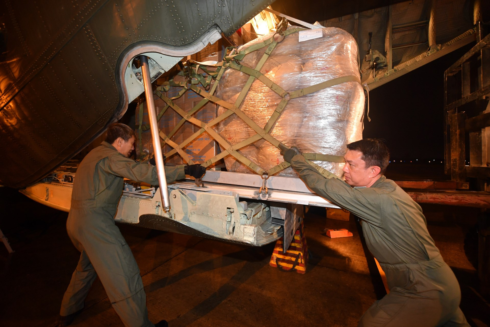 Republic of Singapore Air Force (RSAF) personnel unloading the humanitarian supplies in Vientiane, Laos.
