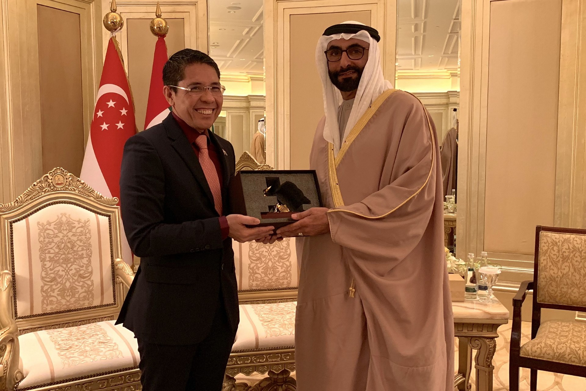 Senior Minister of State for Defence and Foreign Affairs Dr Mohamad Maliki Bin Osman (left) exchanging a token of appreciation
