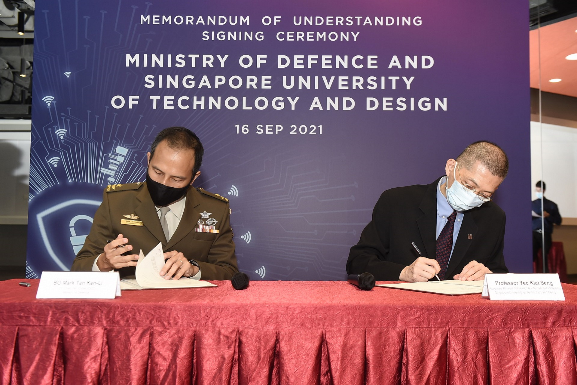 Defence Cyber Chief Brigadier-General Mark Tan (left) signing the Memorandum of Understanding with Singapore University of Technology and Design Associate Provost for Research & International Relations Professor Yeo Kiat Seng (right).