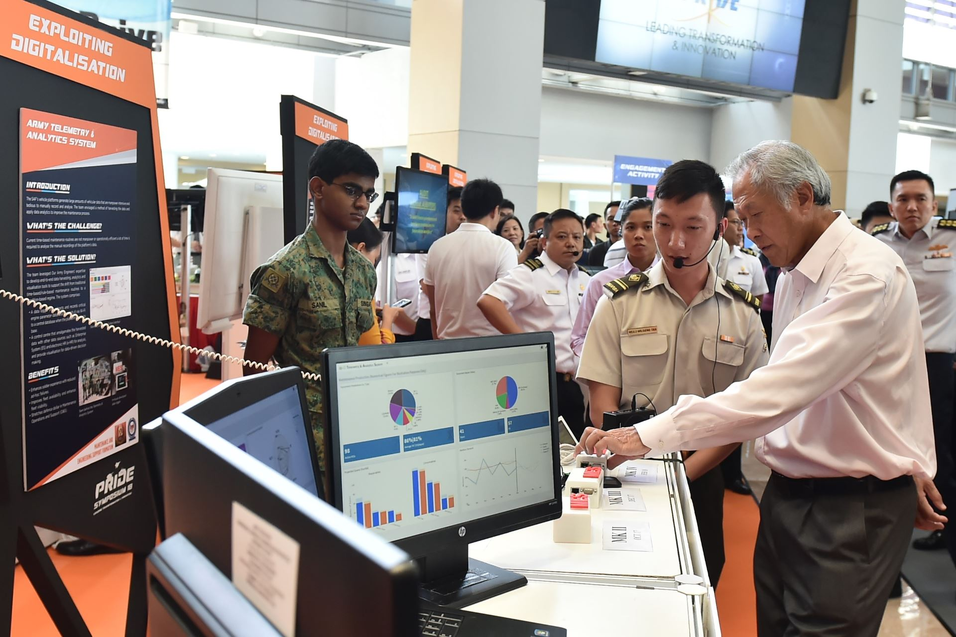 Dr Ng (right) viewing a display of the Army Telemetry and Analytics System during his tour of the PRIDE Symposium 2018 exhibition.