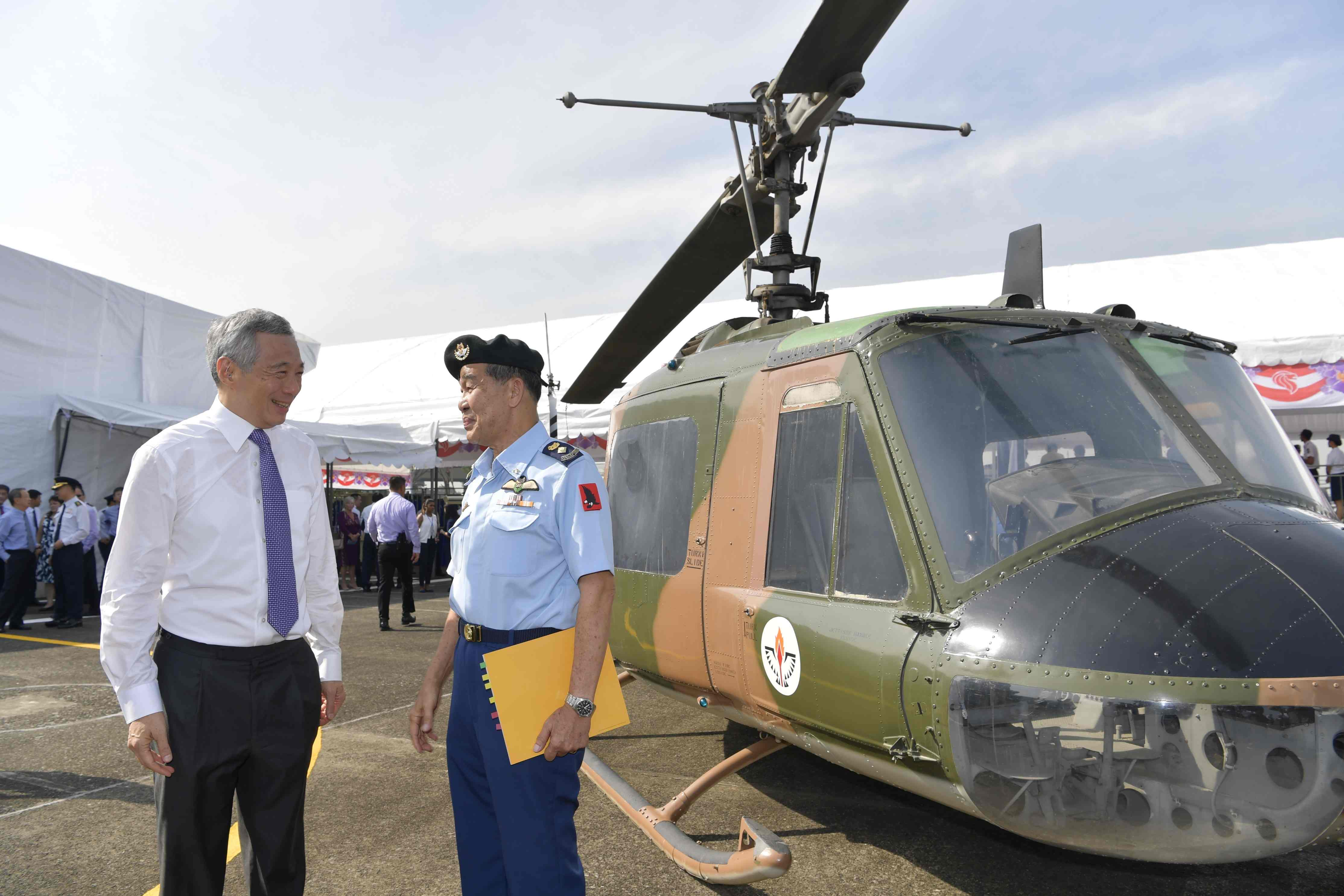 PM Lee interacting with RSAF Pioneer, LTC(Ret) Leo Tin Boon, in front of the UH-1H helicopter.