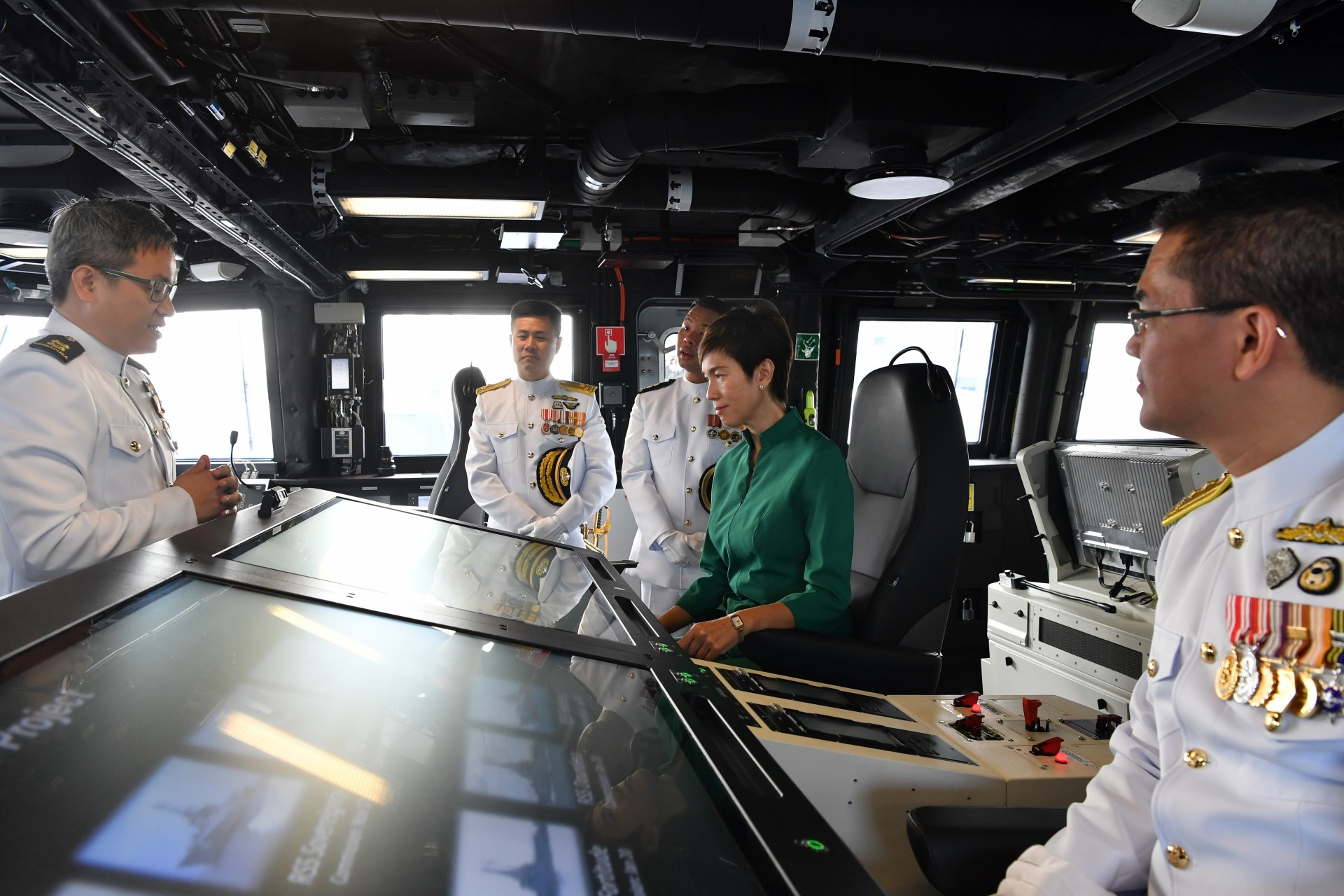Mrs Teo receiving a brief at RSS Dauntless' Integrated Command Centre, accompanied by the Chief of Navy Rear-Admiral Lew Chuen Hong (right).