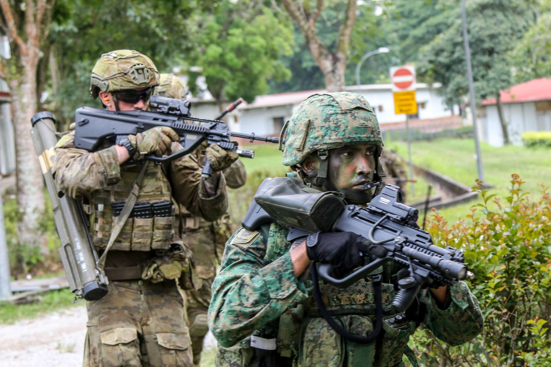 Exercise participants from the Army Deployment Force and the Australian Defence Force's Rifle Company Butterworth preparing to storm a building during the integrated company manoeuvre exercise.