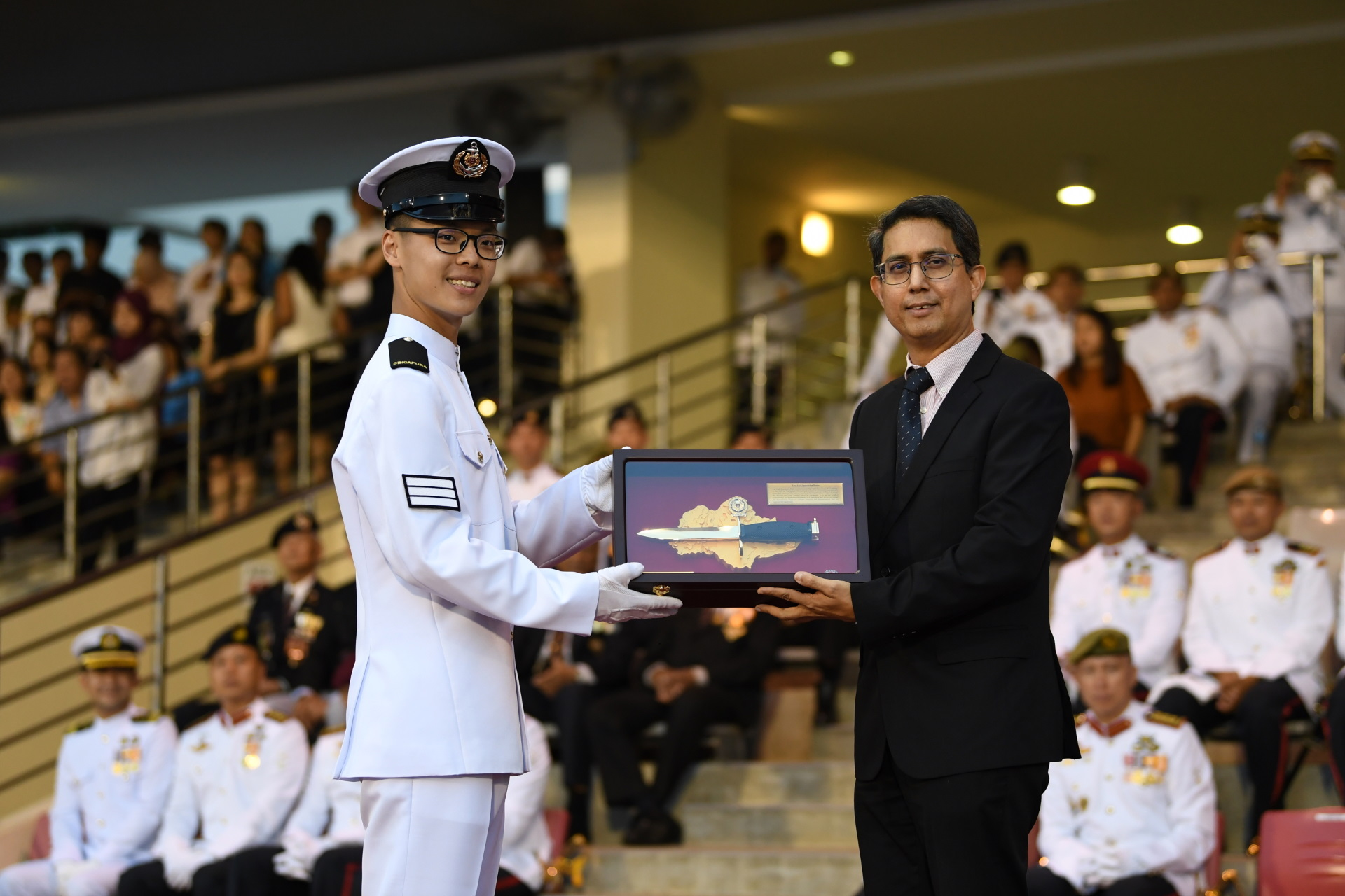 A/P Faishal presenting the Golden Bayonet to Specialist Cadet (SCT) Lee Jing Yuan from the Republic of Singapore Navy.