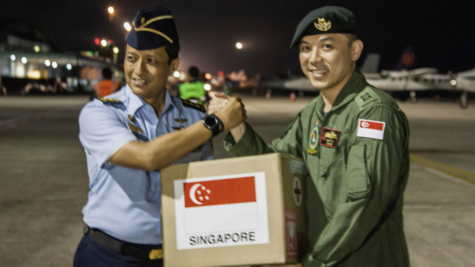 The Singapore Armed Forces Mission Commander, Lieutenant Colonel (LTC) Oh Chun Keong (right) handing over the relief package to LTC Ali Sudibyo, of the Indonesian Armed Forces (left) at Balikpapan Airport, Indonesia.